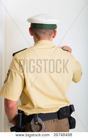 Policial batendo na porta da frente da casa