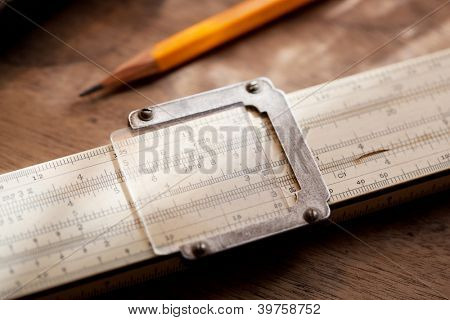 Vintage slide rule on a old work table, with natural lighting.