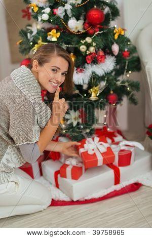 Mujer poner de presente la caja bajo el árbol de Navidad y mostrando Shh gesto
