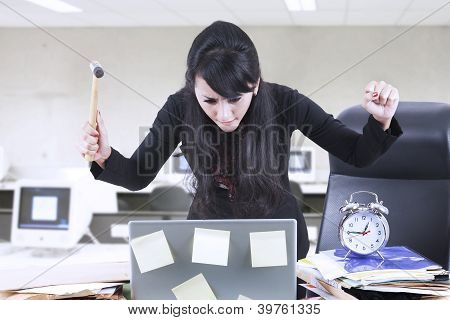 Angry Businesswoman With Hammer And Laptop