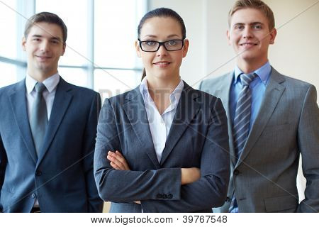 Portrait of a smiling business woman looking at camera with two employees behind