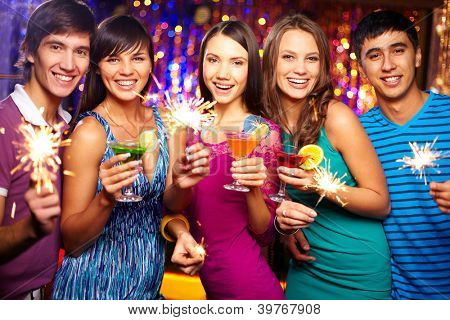 Portrait of joyful friends toasting at New Year party