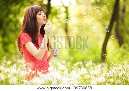 Happy woman blowing bubbles in the park