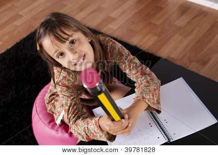 Little girl at her home writing with a giant pencil