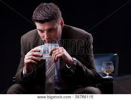 Businessman enjoying drinks and money count
