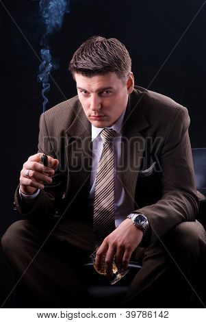 Young businessman sitting on a couch with an drink and a cigar