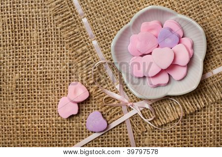 Heart-shaped sweets on sack tablecloth