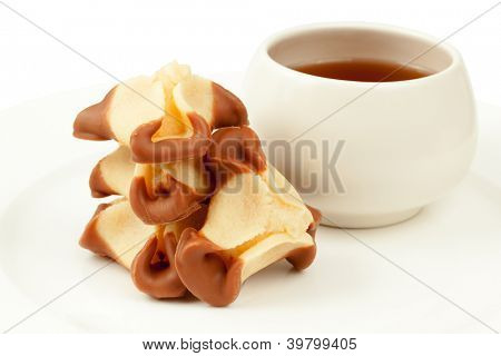 Stack of cookies shaped as tricorn hat and cup of tea on plate