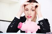 Sad businesswoman looking on piggy bank. Financial crisis concept