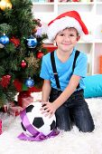 Little boy in Santa hat sits near Christmas tree with football ball