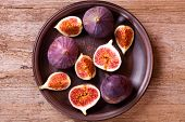 stock photo of dessert plate  - fresh figs in a plate on rustic wooden table - JPG