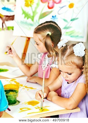 Child painting at easel in school.