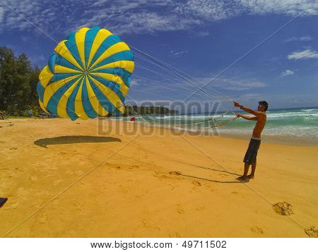PHUKET THAILAND AUGUST 6: Unidentified man prepares a parachute for tourists on the beach, on August 6, 2013 at Kata Beach in Phuket Thailand.