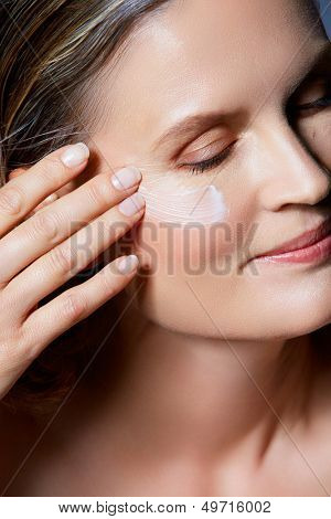 beautiful forty year old woman with natural makeup and healthy skin texture with cream on her face, on blue gray studio background