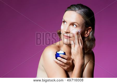 beautiful forty year old woman with natural makeup and healthy skin texture on pink studio background. Applying facial cream from a cosmetics tub