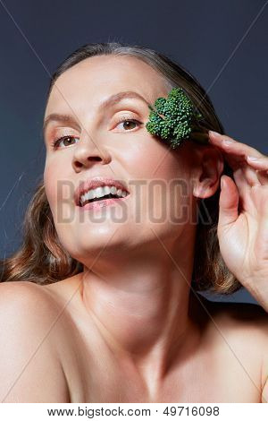 beautiful fourty year old woman with natural makeup and healthy skin texture on blue gray studio background holding a broccoli in her hand