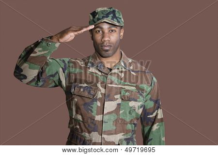 Portrait of a young African American US Marine Corps soldier saluting over brown background
