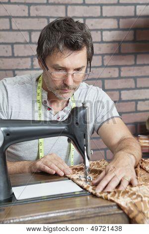 Mature male dressmaker stitching cloth on sewing machine
