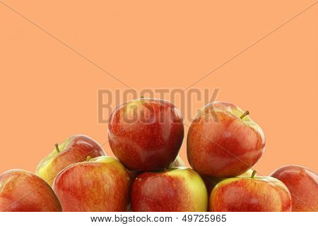 Bunch of fresh Braeburn apples on an orange background with copy space
