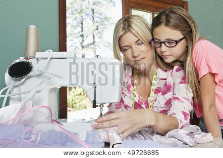 Little girl looking at mother sewing cloth