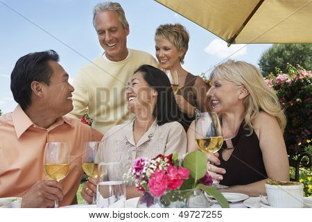 Group of multiethnic friends enjoying drinks at dinner table outdoors