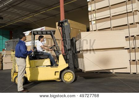 Warehouseman and forklift truck driver working in timber factory