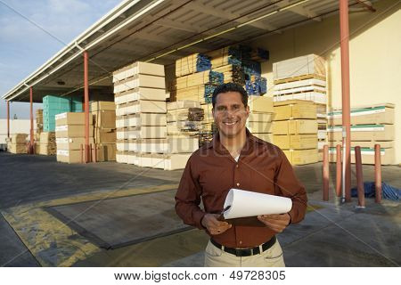 Portrait of happy middle aged man with clipboard standing in front of timber factory