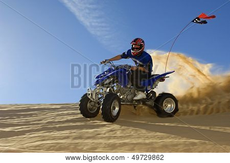 Young man riding quad bike in desert