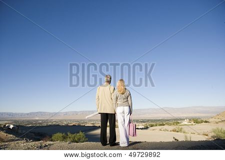 Rear view of middle aged couple looking at plot for new home