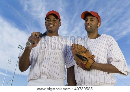 Low angle portrait of baseball team mates against cloudy sky