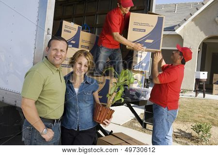 Happy couple with delivery men unloading moving boxes from truck into new house