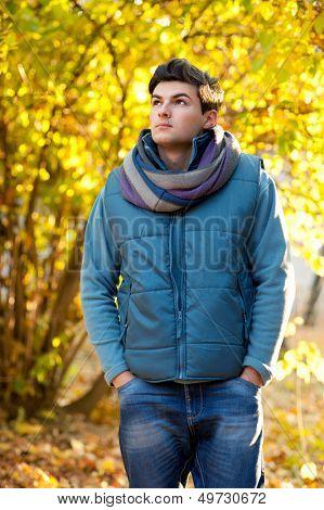 Handsome man walking in autumn park.