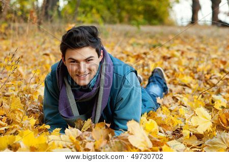 Young smiling man portrait in autumn park. Outdoor.