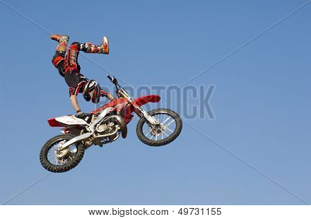 Low angle view of motocross racer performing stunt with motorcycle in midair against clear blue sky