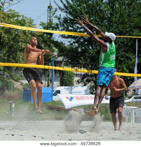 KAPOSVAR, HUNGARY - AUGUST 4: Leonel Munder (in green) in action at a ROAK Viragfurdo Kupa beach volleyball competition, August 4, 2013 in Kaposvar, Hungary.