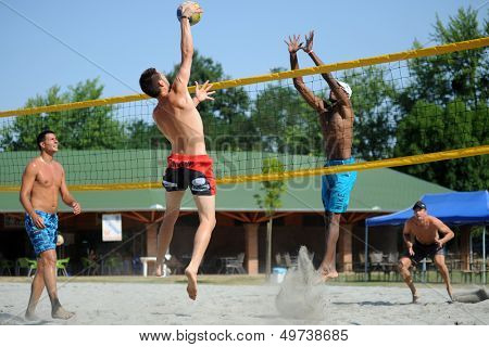 KAPOSVAR, HUNGARY - AUGUST 4: Tamas Kaszap (with ball) in action at a ROAK Viragfurdo Kupa beach volleyball competition, August 4, 2013 in Kaposvar, Hungary.
