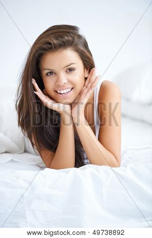 Vivacious young woman in bed lying on the bedclothes on her stomach with her chin on her hands giving the camera a beautiful smile