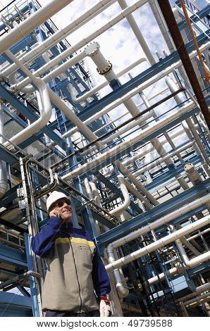 refinery worker with giant pipelines construction, oil and gas industry
