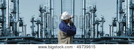 oil and gas worker pointing at large industrial refinery installation