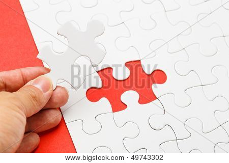 Incomplete puzzle with missing piece on human hand