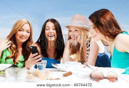 summer holidays, vacation and technology - girls looking at smartphone in cafe on the beach