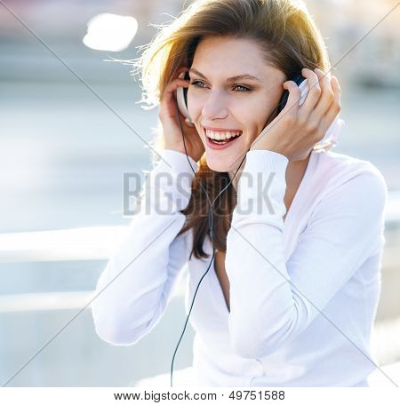 Pleasant young woman puts her headphones on