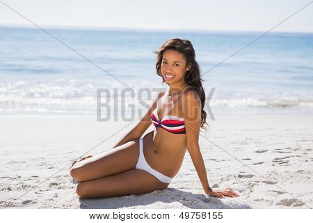 Sexy tanned woman in bikini smiling at camera while posing on the beach