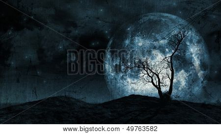 Grunge background of a spooky silhouette of a tree against a large moon in a night sky