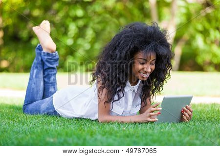 Outdoor Portrait Of A Teenage African American  Girl Using A  Tablet