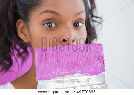 Pretty woman holding paintbrush with pink paint on her nose looking at camera