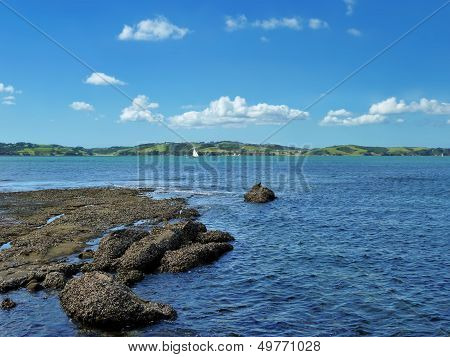 View From The Shore Onto The Sea With An Island In The Background