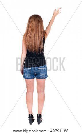hintere Ansicht der Frau. Junge Frau in Jeans drückt etwas nach unten. Gegenüber dem weißen Hintergrund isoliert.