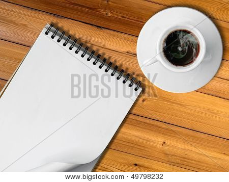 Notebook And White Cup Of Hot Coffee