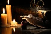 stock photo of inkpot  - Vintage still life with candles near quill pen and books on dark background - JPG